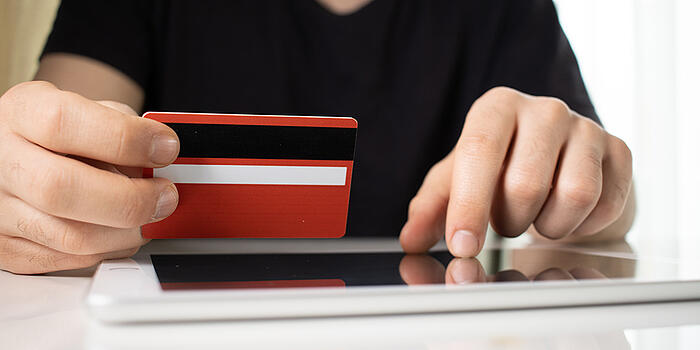 person-holding-red-credit-card-over-tablet-on-white-surface