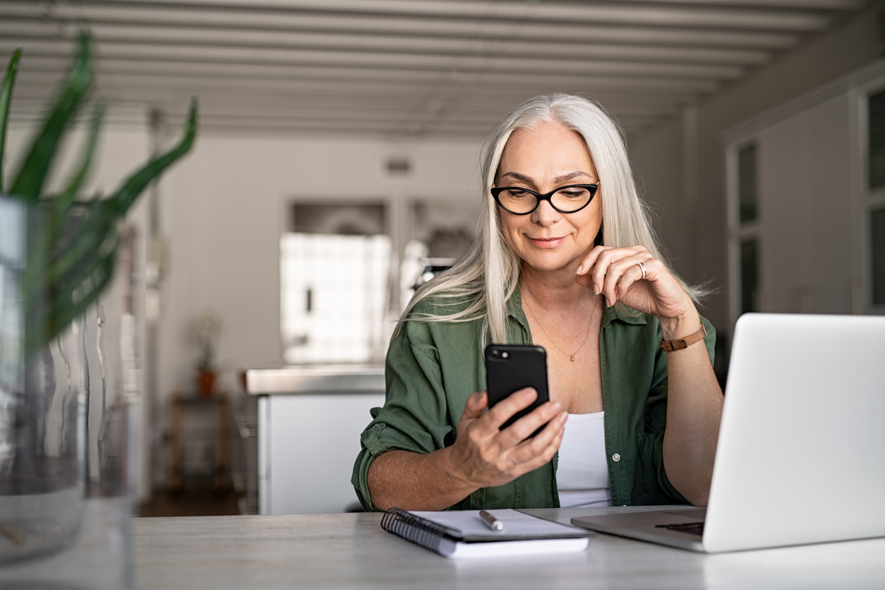 woman wearing glasses looking at her phone